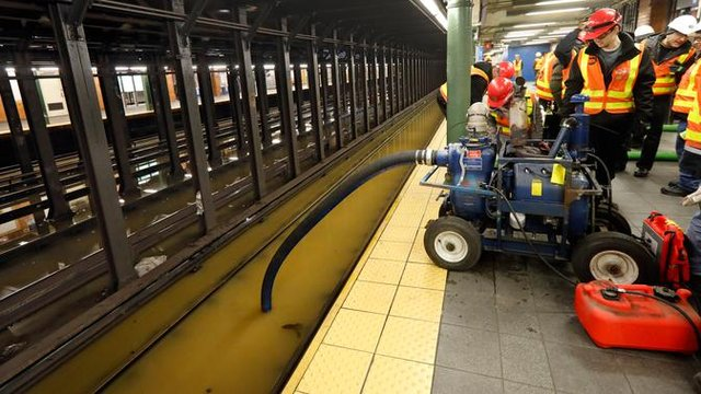 Para pekerja menyedot air dari stasiun kereta bawah tanah Lincoln Center yang banjir di New York, Amerika Serikat, Senin (13/1/2020). Genangan air menghambat layanan kereta bawah tanah pada jam sibuk. (AP Photo/Richard Drew)