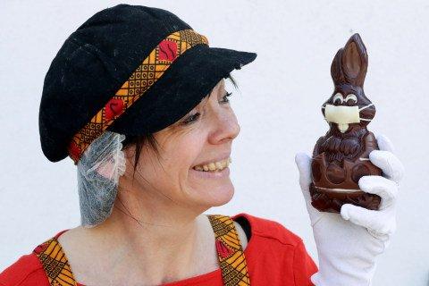 Seorang seniman memperlihatkan coklat kelinci Paskah yang menggunakan masker di pembuatan cokelat Belgia Genevieve Trepant, Lonzee, Belgia. Foto: REUTERS/Yves Herman
