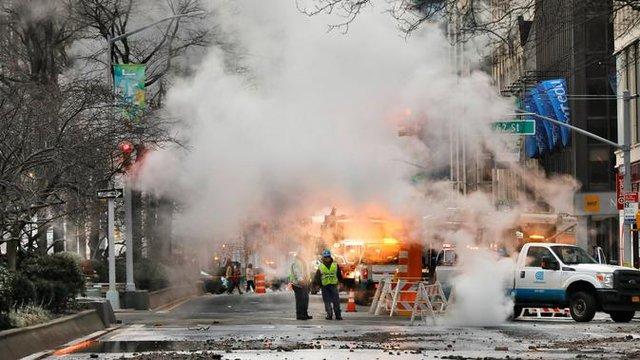 Asap mengepul dari jalan saat sejumlah kendaraan terpaksa berhenti karena banjir di New York, Amerika Serikat, Senin (13/1/2020). Banjir diakibatkan rusaknya saluran air utama yang berdiameter tiga kaki. (AP Photo/Richard Drew)