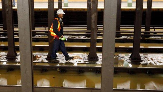 Pekerja memeriksa stasiun kereta bawah tanah Lincoln Center yang banjir di New York, Amerika Serikat, Senin (13/1/2020). Genangan air menghambat layanan kereta bawah tanah pada jam sibuk. (AP Photo/Richard Drew)